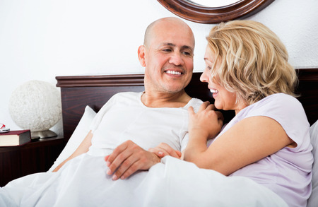 awaking: Cheerful mature loving couple lounging in bed after awaking cuddling Stock Photo