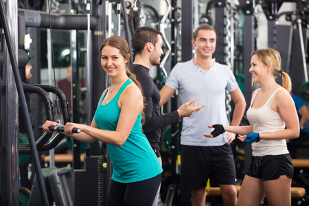 anaerobic: Young adults doing powerlifting on machines in fitness club