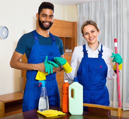 dusting: Positive young cleaners cleaning and dusting in ordinary house