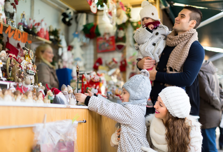 thirties: A young and beautiful woman in her thirties buying christmas decorations with her husband and children. Selective focus on woman.