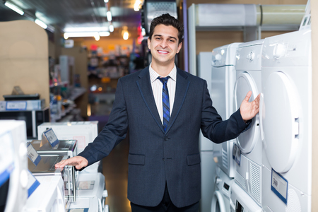 sales manager: Cheerful sales manager showing goods at household appliances section in hypermarket