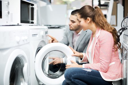 clothes washer: Positive young family couple buying new clothes washer in supermarket. Focus on the woman Stock Photo