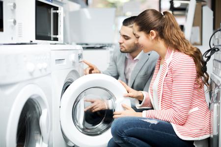 lavadora con ropa: Positivo pareja joven familia la compra de nueva lavadora de ropa en un supermercado. Centrarse en la mujer Foto de archivo