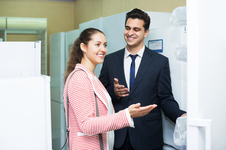 spouses: Happy spouses buying domestic refrigerator in supermarket