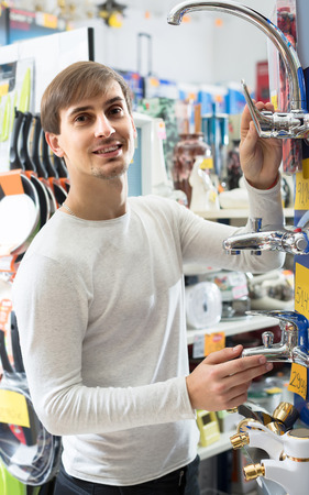 russian man: Handsome young russian man buying new water cock in supermarket