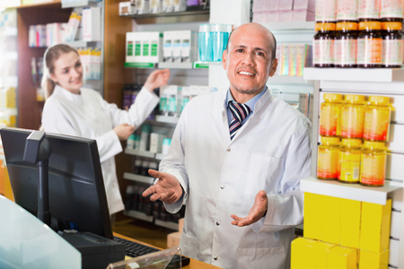 dispensary: Friendly professional pharmaceutists at reception of drugstore ready to help Stock Photo