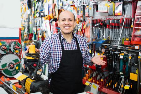 seller: Smiling elderly seller posing near electric compressor in household store Stock Photo
