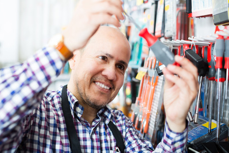 tooling: Portrait of positive seller offering working tooling in household store Stock Photo