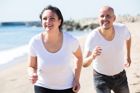 2 50: Cheerful adult couple in white T-shirts jogging together in the good weather. Focus on woman Stock Photo