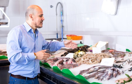 cooled: Elderly man choosing cooled seafood in fish store and smiling
