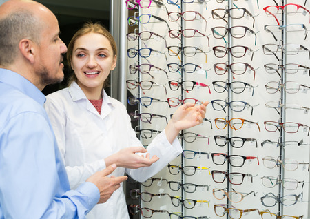 25s: Friendly young female optician offering glasses frames to mature male customer