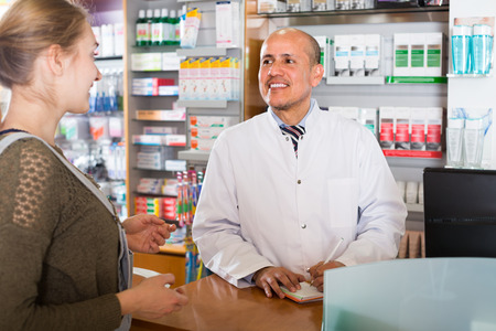 farmacy: Experienced pharmacist counseling female european customer in modern farmacy