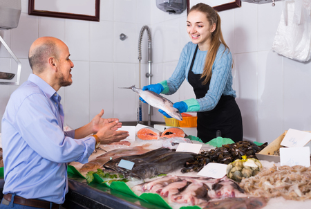 cooled: Mature spanish  male customer selecting cooled fish in local fishery