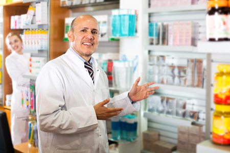 farmacy: Cheerful mature pharmacist and female assistant working at farmacy reception Stock Photo