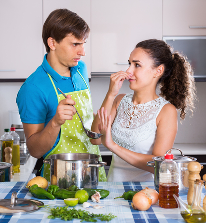 stinking: Portrait of family couple with stinking meal in domestic kitchen