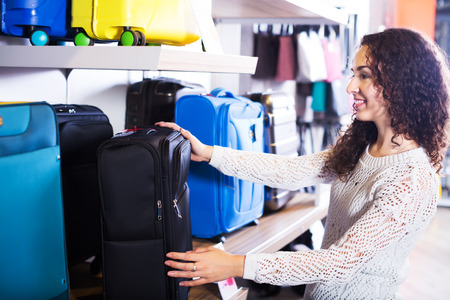 haberdashery: Young happy woman selecting travel suitcase in haberdashery shop Stock Photo
