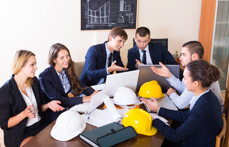 specialists: Portrait of specialists with helmets and laptops having meeting indoors Stock Photo