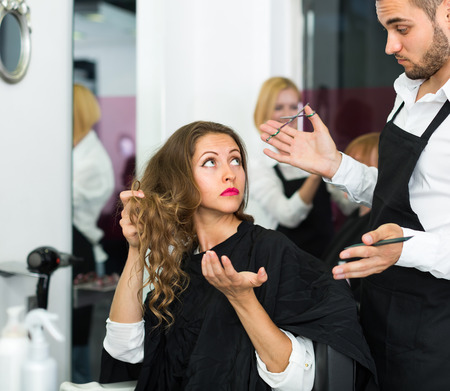 negatively: Displeased young female client negatively talking with the hairdresser Stock Photo