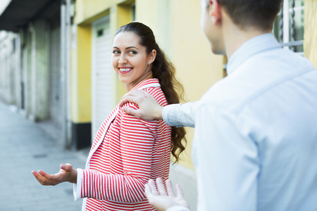 sidewalk talk: Cheerful man chasing pleased smiling brunette woman and flirting outdoor Stock Photo