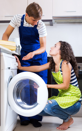 serviceman: Young serviceman and unhappy girl standing near washing machine indoors. Focus on the woman
