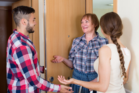 threshold: Smiling mature woman visiting happy young family