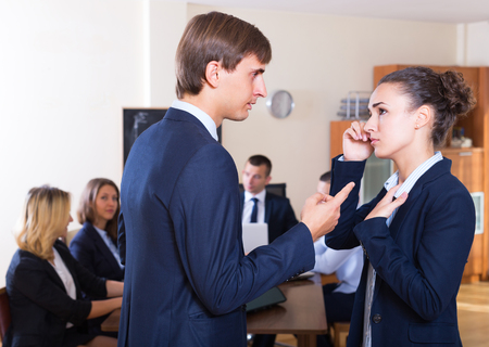 severely: Manager severely lecturing female employee for mistake at office meeting. Focus on man