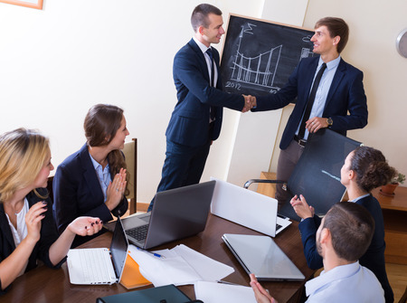 workgroup: Firm handshake between two business partners at team meeting Stock Photo