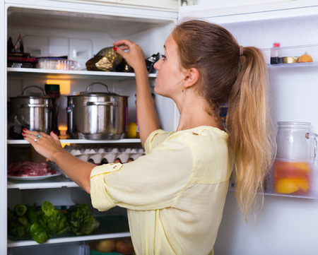 woman searching: Positive woman searching products on refrigerator shelves Stock Photo