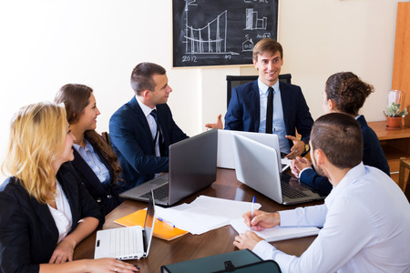 subordinate: Happy boss with subordinate officials discussing long-term forecast and smiling Stock Photo