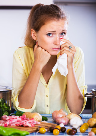 weary: Weary girl with meat and vegetables at kitchen table