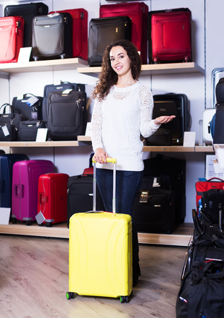 haberdashery: Young positive woman choosing travel suitcase in haberdashery store