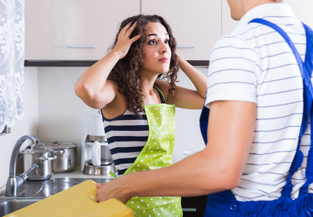 bribes: Unprofessional adult russian plumber asking furious young woman for bribes indoors