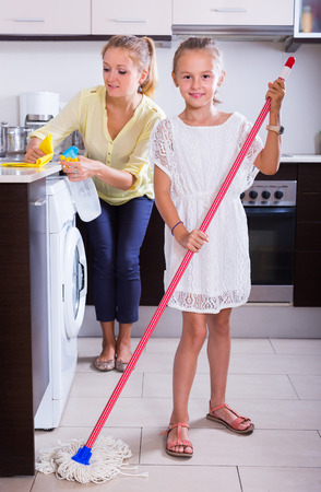 cleanup: Happy mother and daughter doing regular cleanup together at kitchen. Focus on girl Stock Photo
