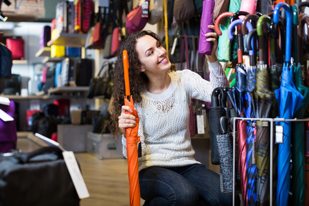 haberdashery: Young smiling brunette woman purchasing automatic umbrella in haberdashery shop
