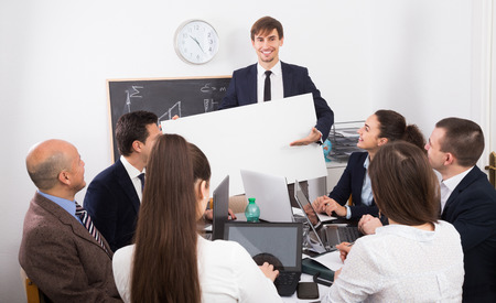 new products: Friendly people presenting new products plan at poster during conference  indoors Stock Photo