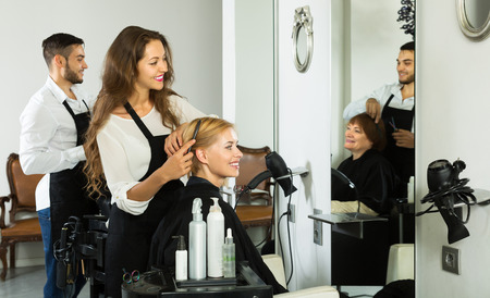 haircutter: Smiling woman hairdresser doing hairstyle for young men