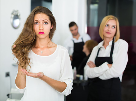 hairdressing salon: Portrait of unhappy young longhaired girl at the hairdressing salon Stock Photo