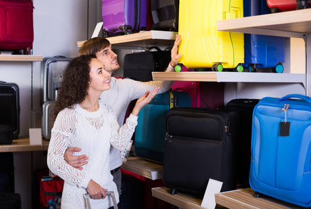 shopgirl: Positive european customers looking at roll-aboard bags in store Stock Photo