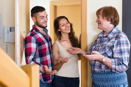 threshold: Happy senior woman meeting  young couple at the door Stock Photo