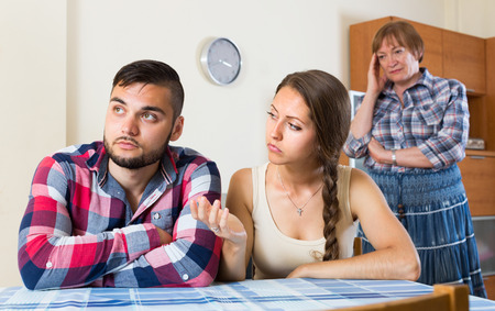displeased: Conflict between displeased young couple and elderly female at home. Selective focus Stock Photo