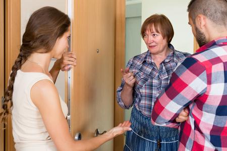 threatens: Displeased elderly female threatens her young neighbors at the door