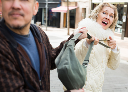 accosting: Portrait of frightened mature woman and robber stealing bag