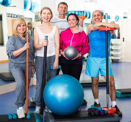 workouts: Mature men and women after exercising in  gym with sport equipment