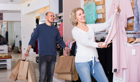 indignant: Frustrated mature husband tired awaiting his wife shopping in clothing store Stock Photo