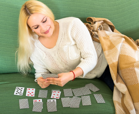 woman couch: Young woman with gorgeous long blond hair on a couch at home playing solitaire Stock Photo