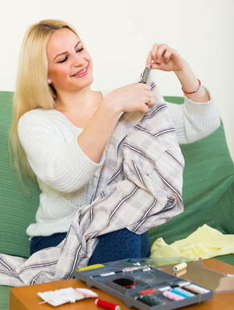 mending: Attentive  american girl on couch mending linen and smiling Stock Photo