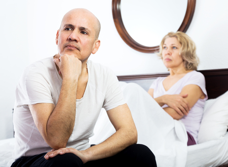 impotent: Sad man and woman getting through scandals and blamings in bedroom