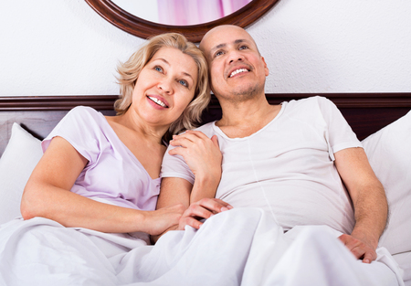 awaking: Positive cheerful smiling mature loving couple lounging in bed after awaking cuddling