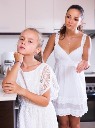 berate: Crisis of motherhood: sad woman preaching upset little daughter Stock Photo