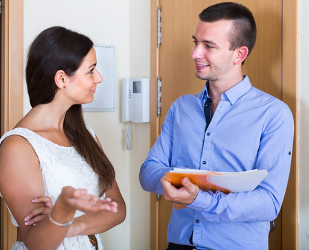 householder: happy american agent greeting householder and bagging subscriptions in hall Stock Photo